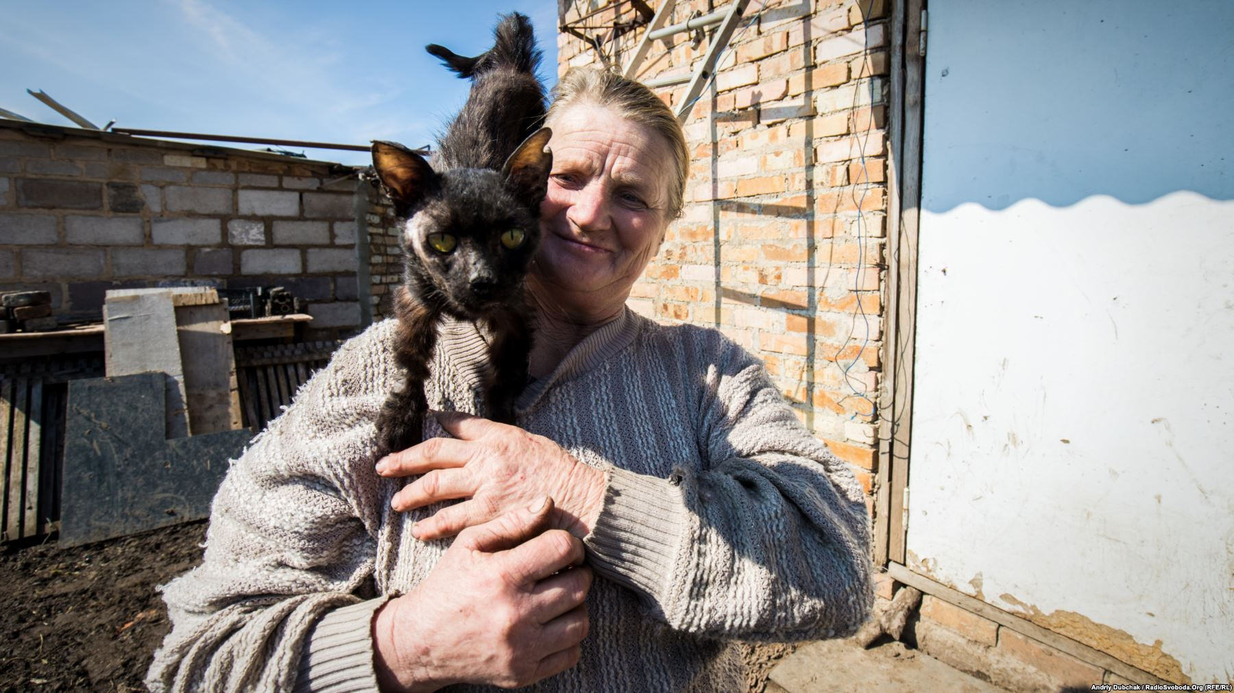 "Kral with her cat, Timka. The cat was discovered badly wounded ""with blood covering half of its face"" after a recent battle, and Kral is now nursing him back to health. Photo by: Andriy Dubchak"