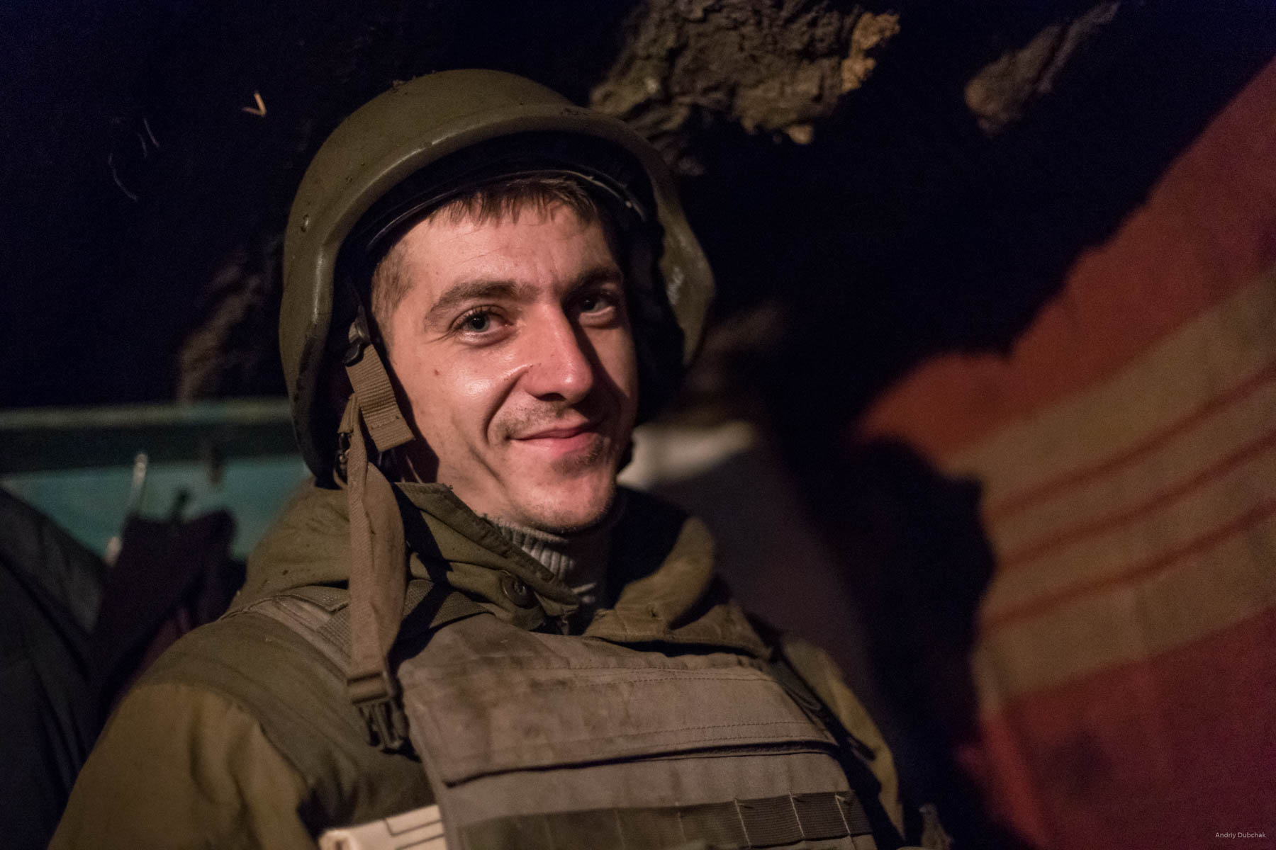 A fighter smiles, who came in for a moment to the dugout during a night battle, near Popasnaya, December 2017.