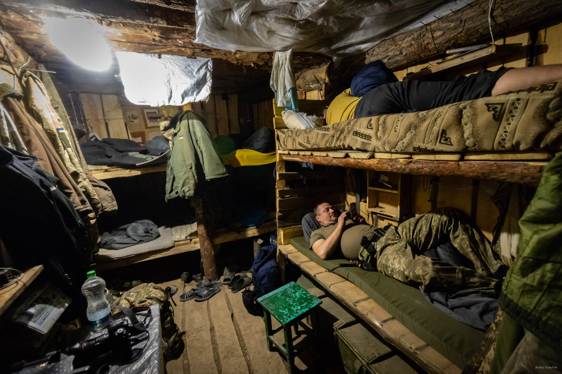 """After a four-hour watch, we return to a """"sleeping dugout"""" that contains 10 beds. The warriors rest here between duty calls. Standard dugout accommodates from 6 to 10 fighters. There are, of course, smaller. According to the rules, there are two entrance/exits. It happens that a dugout has several rooms(It depends on how big a hole was dug and how much construction materials were available). We even saw «shelters-gyms. »   District of Popasnoy, December 2017"""