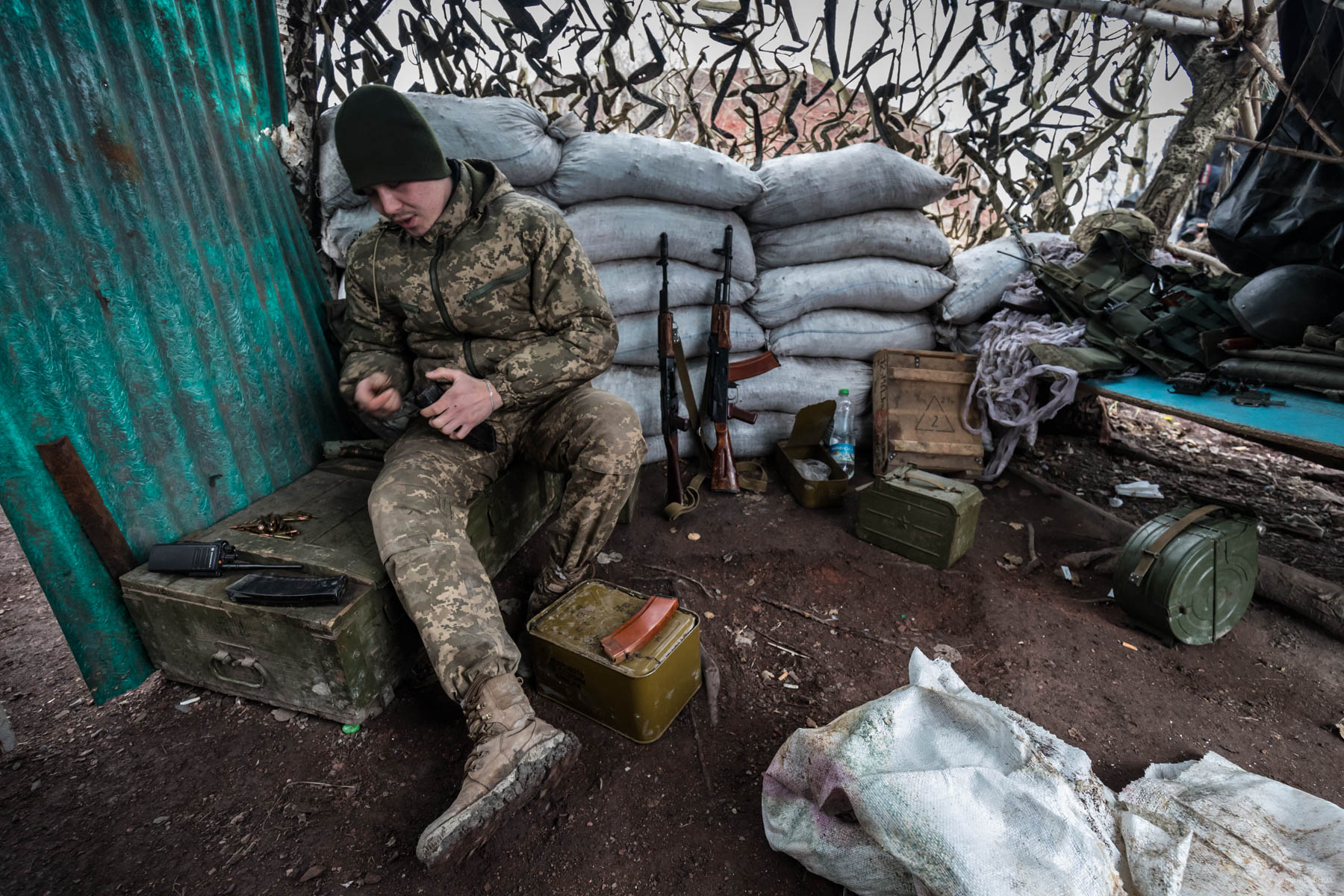 """Alexander, a fighter from Kherson, reloads his assault rifle dispenser magazine on a position reinforced with refuse stone bags, on the gob pile near a town Zolote. - Do you want to go home? Sasha smiles: - I feel sad at home. In addition, here are our boys. It's OK.  The guy is 20 years old. In a conversation, he often uses the phrase """"It's OK.""""    District of Popasnoy, December 2017"""