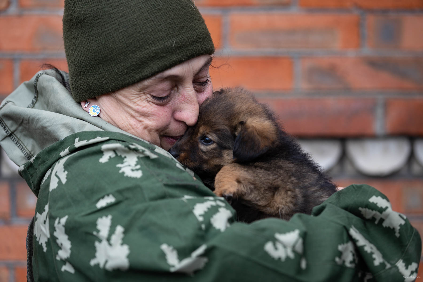 """A combat medic, """"Viktorovna,"""" is playing with Fly the puppy, before traveling to a concert in Mariupol. Soldiers prepare food themselves. Since the boys are mostly young, they often eat """"what is available"""", """"not bothering"""" themselves with cooking. Probably, that is why a single woman here, the combat medic of the company, """"Victorovna"""", who always cooks a lot of very tasty foodstuff, has guests in the house all the time, especially in the kitchen ... :) In all the shelters and basements, many animals (cats, dogs) live with fighters. As a rule, if there are dogs - there are no cats. And vice versa. Shirokine, March 2018."""