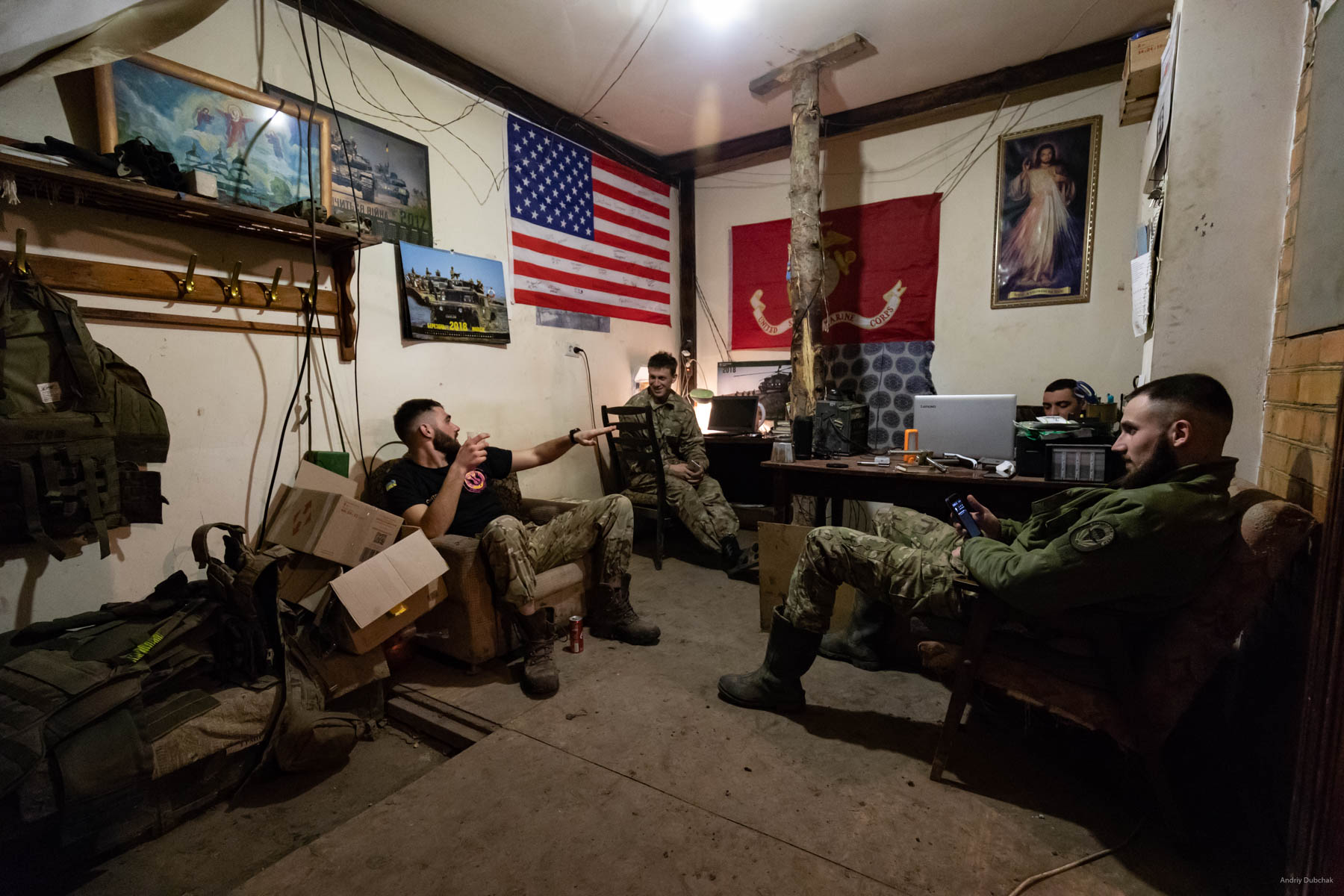 Marines converse in one of the basements in Vodyane. In the background, there is a portion of the US flag can be seen, donated by the American Marines to the Ukrainian ones, during joint exercises. The photo was taken in March, during our next visit in June, this house was gone. The enemy broke it by his mortars. Fortunately, the first mine that fell next to the house gave time for everyone to jump into the basement. Vodyane, March 2018.