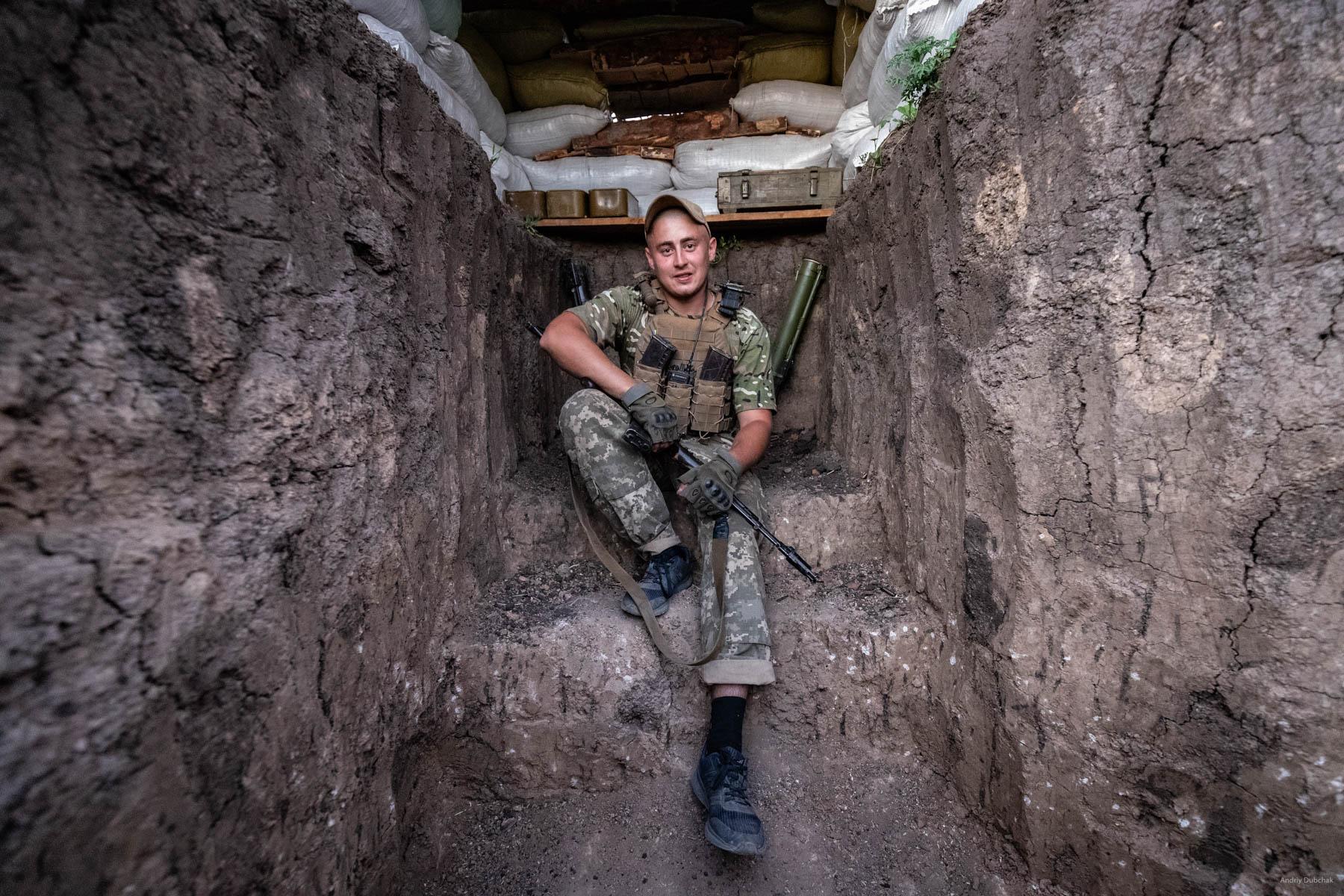 "Section commander, ""Yarik,"" is in the newly built gun nest on the front in the fields, near Vodyane. Vodyane, June 2018."