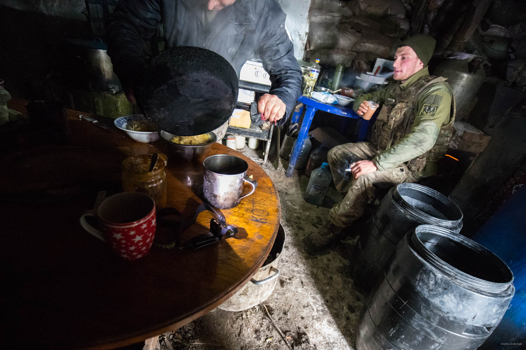 """A marine drinks coffee and smokes in a kitchen-dugout, near Shirokine. Local """"club"""" - a kitchen, some people are always there, the place you can eat at(they cook all the time), drink coffee with a cigar (almost everyone smokes), talk. Usually there is good Wi-Fi. Shirokine, March 2018."""