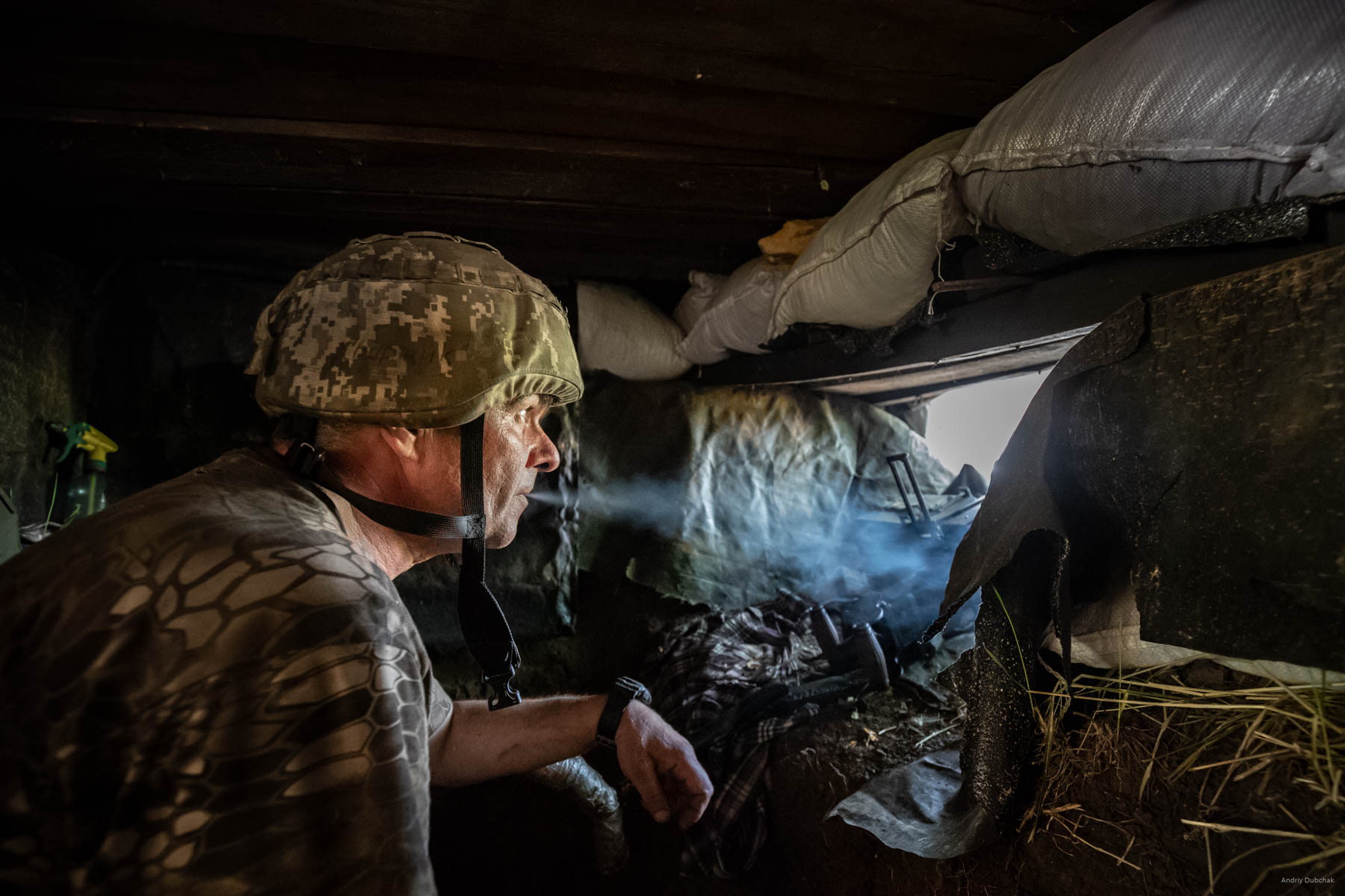 """Ukrainian soldiers use DSHK (large-caliber machine gun) to """"probe"""" enemy in order to reveal his gun emplacements. After a machine gun burst, a 55-years-old warrior soldier named «Svarschik» from Dnepr observes enemy gun emplacements. After the firefight, he says, """"I am a pipe welder. I could have been welding a pipe in Norway, but I am here."""" Settlement Pivdenne, near Gorlivka on June, 17th, 2018"""