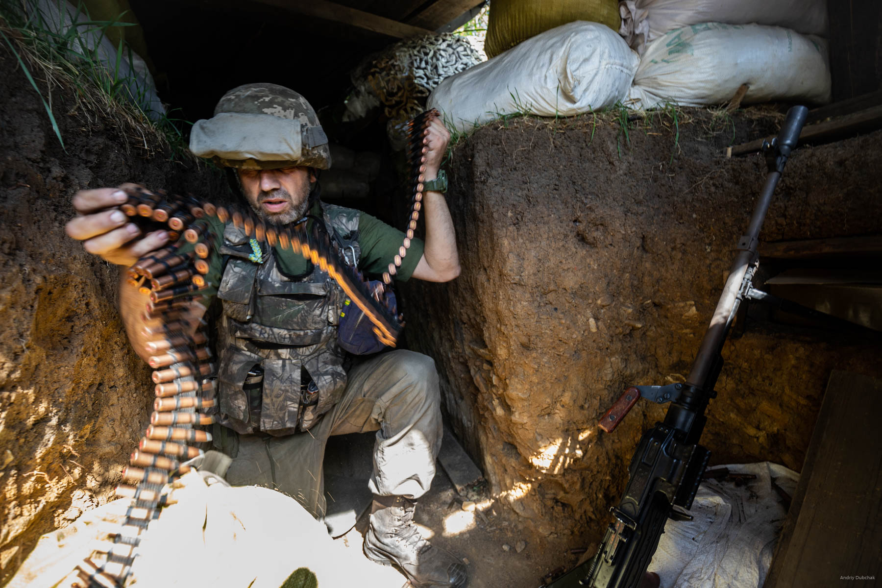 The enemy began to shoot back from infantry weapons. A Kalashnikov's machine gun joins DSHK in the firefight. Bullets buzz and squeal above our position. The warriors strive to spare the rounds, but the rate of fire grows and machinegun belts are replaced (in the photo). Settlement Pivdenne, near Gorlivka on June, 17th, 2018