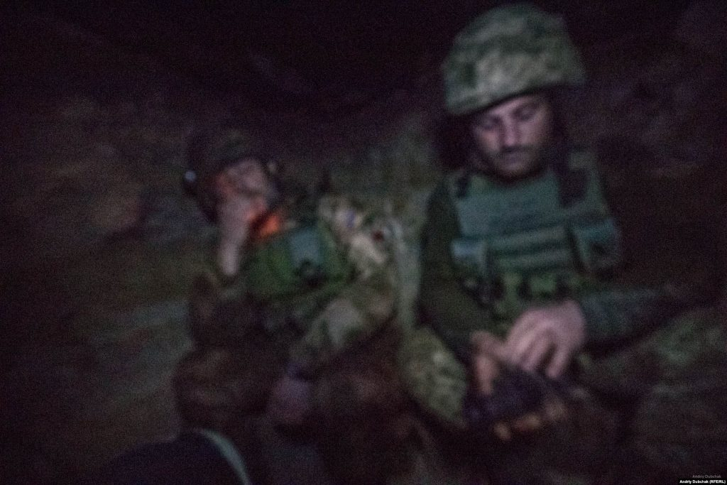 In the darkness of a dugout near Bakhmut in December 2017. Photo: Andriy Dubchak