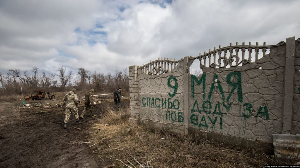 "Ukrainian soldiers walk past a fence in Shyrokyne with a message written by Russia-backed separatists: ""May 9, Thank your grandfather for the victory!"" in reference to the 1945 Soviet victory over Nazi Germany. Photo Andriy Dubchak"