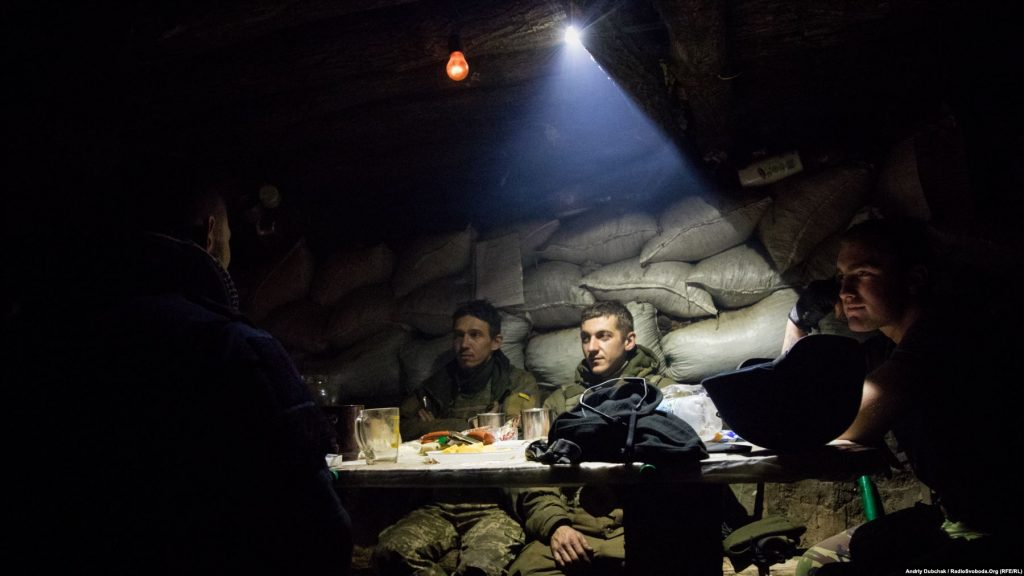 At a position near Bakhmut, Ukrainian soldiers eat dinner as their comrades-in-arms trade bursts of fire with Russia-backed separatists. Photographer Andriy Dubchak