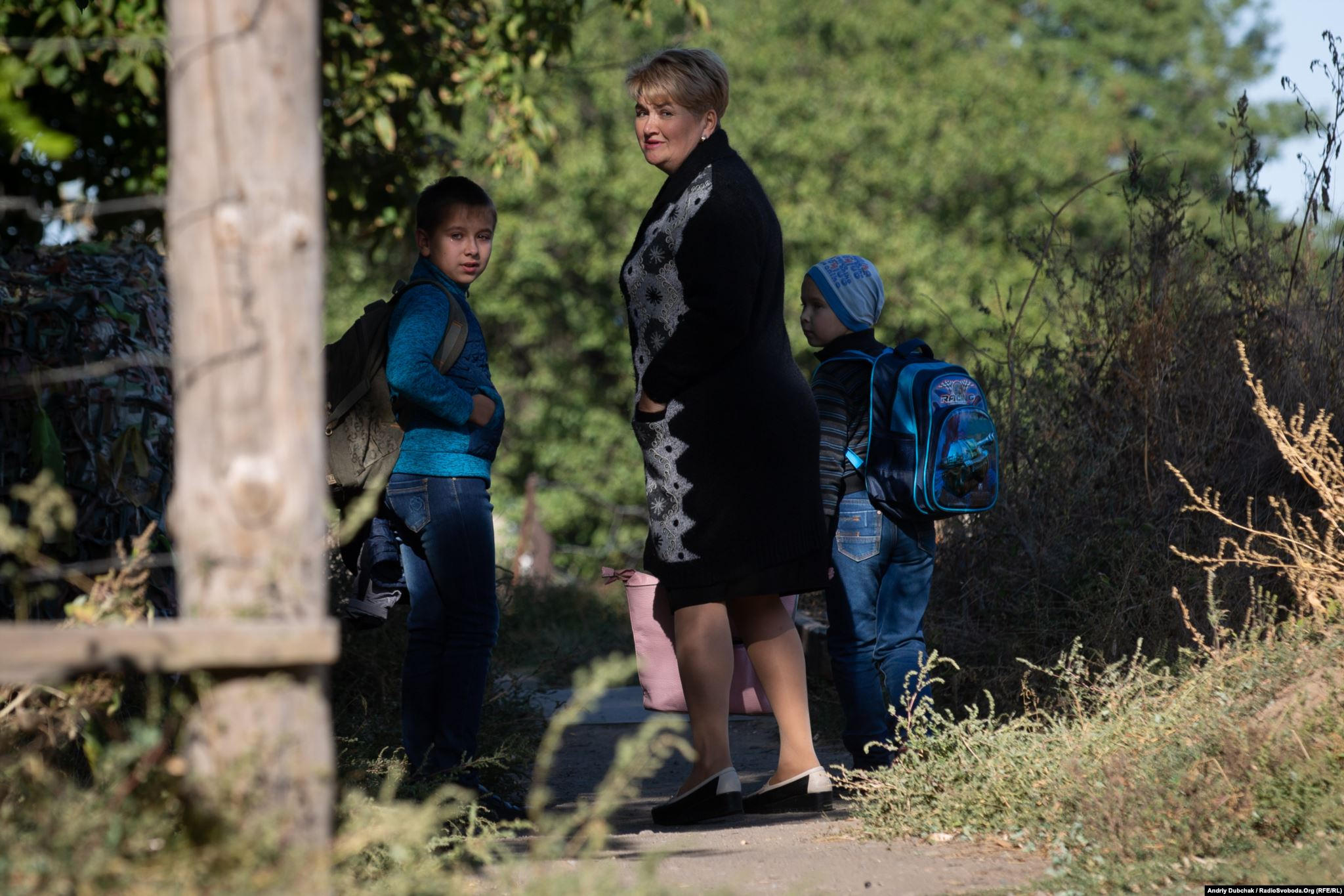Misha, Stanislav, and their aunt Tetyana, stand in front of the bridge over the Kalmius River. (photo: Andriy Dubchak)