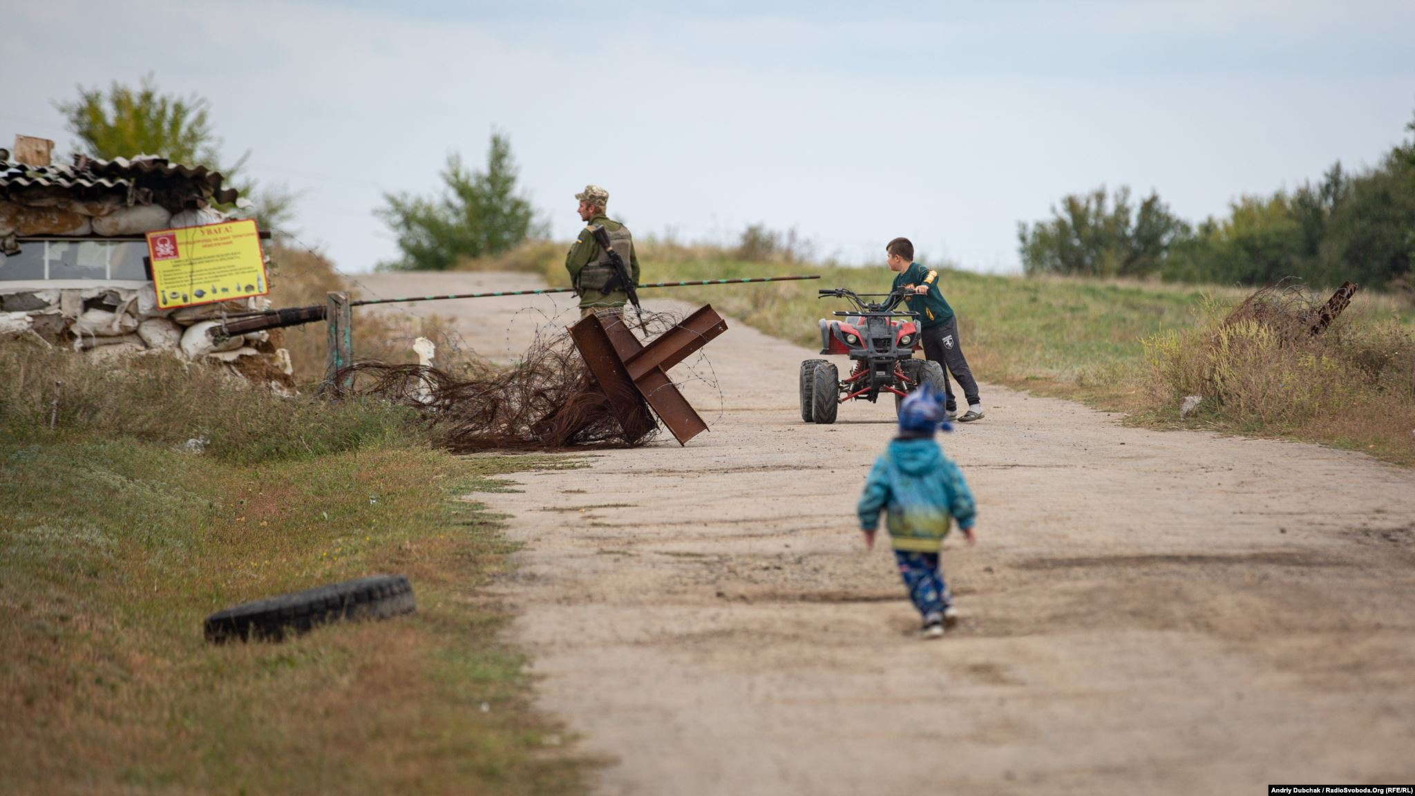 Ten-year-old Davyd rides a mini-quad bike while Stepan tries to catch up. Children are not permitted to go beyond the Luhanske checkpoint. (photo: Andriy Dubchak)