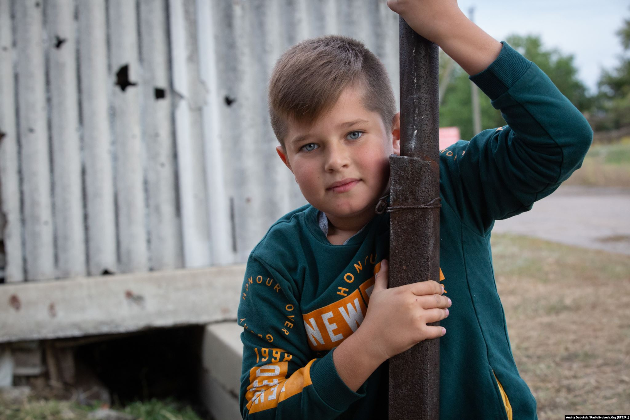 Davyd, 10, wants to be a lawyer and to go to sea. The fence behind their house in Luhanske is full of holes from a mine explosion. (photo: Andriy Dubchak)