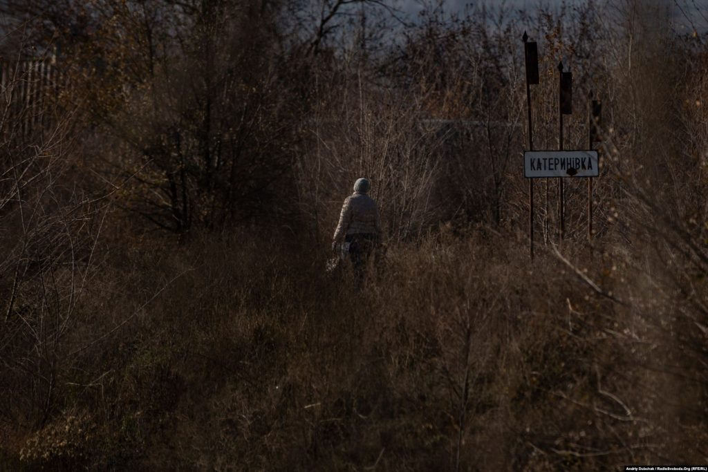 Доступ до Катеринівки можливий як на транспорті, так і пішки. Село починається за сотню метрів від КПВВ. На фото – жінка з торбами йде з Золотого у тепер уже «напівсіру» Катеринівку. Золоте (кореспондент Андрій Дубчак)