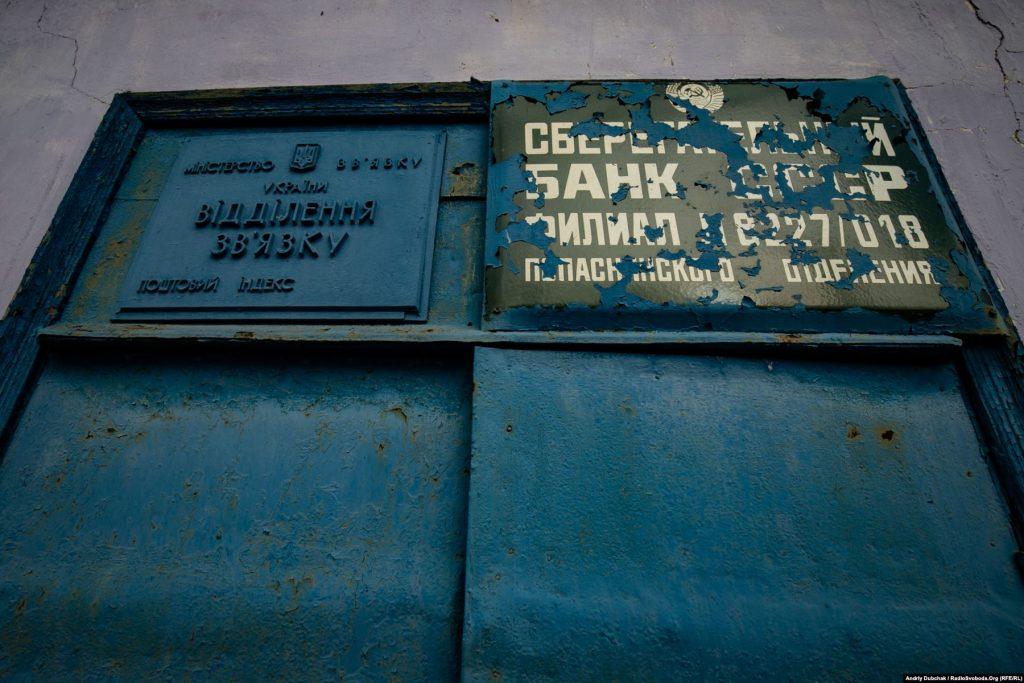 Дві вивіски, одна з гербом України, інша з гербом СРСР, також досить наочно ілюструють стан справ тут. Золоте (фотограф Андрій Дубчак)