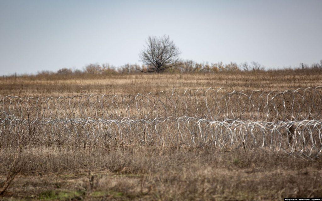 Ряди колючого дроту в полі перед новими позиціями української армії, далі – демілітаризована зона (кореспондент Андрій Дубчак)