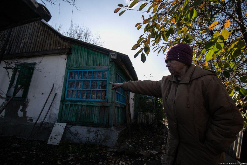 71-річна Любов Семенівна розповідає і показує нам наслідки обстрілу її хати зі стрілецької зброї пару днів тому (28 жовтня). Кулі калібру 7,62 посікли стіни й дах.  Золоте (фотограф Андрій Дубчак)