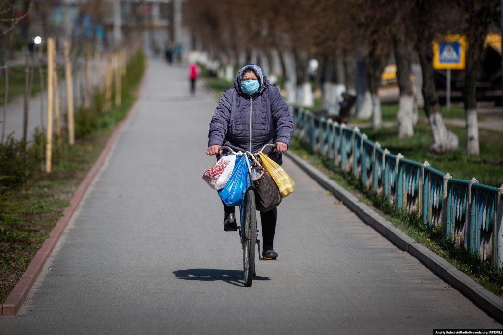 Жінка на велосипеді їде алеєю біля Машинобудівного заводу. Фото - Андрій Дубчак