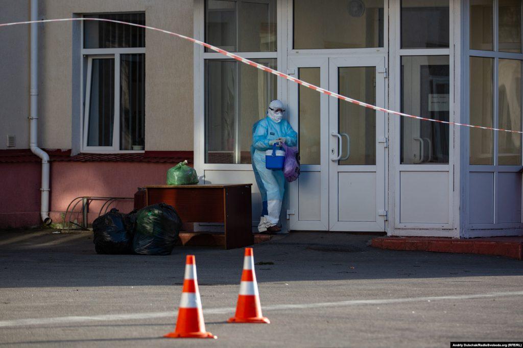 Медичний працівник у антивірусному захисному комбінезоні забирає ліки та передачі для хворих. Фото - Андрій Дубчак