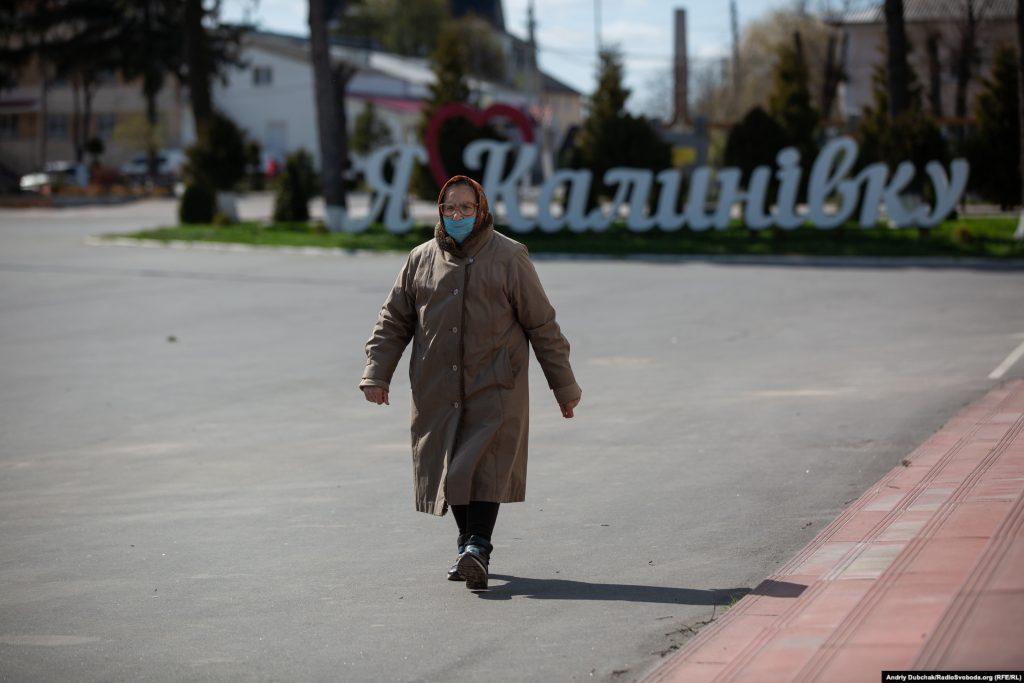 Жінка у медичній масці йде повз інсталяцію «Я люблю Калинівку». Фото - Андрій Дубчак