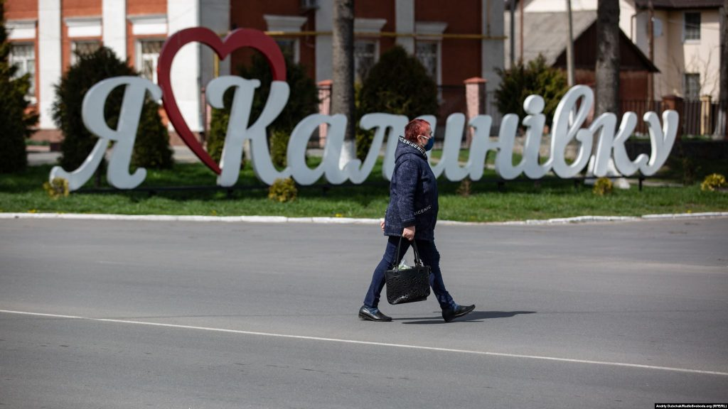 "A woman walks past a sign saying ""I love Kalynivka."" Dubchak says there are many unanswered questions about the pandemic -- like how the coronavirus arrived in the town, why so many medical staff have gotten sick, when Kalynivka's quarantine will end, and how the looming economic crisis will be managed.  Photographer Andriy Dubchak / Ukraine"