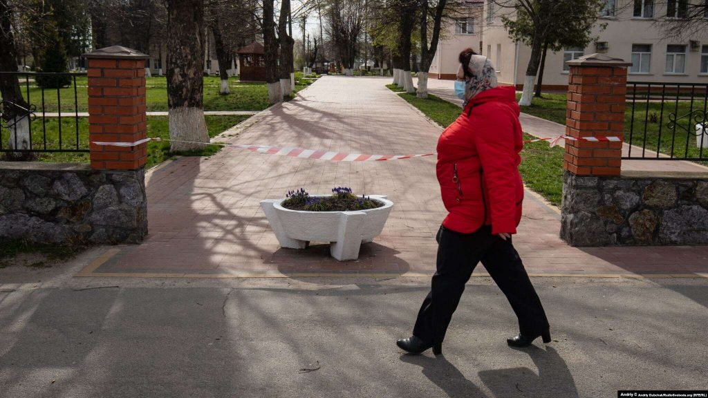A woman walks past the entrance to the hospital in Kalynivka. Dubchak says the town of 20,000 people where he grew up has been transformed by the virus. Streets are largely empty and police in patrol cars use loudspeakers to urge people to stay indoors.  Photographer Andriy Dubchak / Ukraine