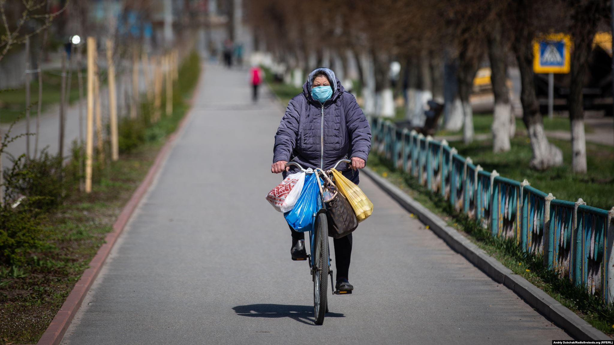 An elderly woman cycles through Kalynivka. All public transport in the town has been suspended. Photographer Andriy Dubchak / Ukraine