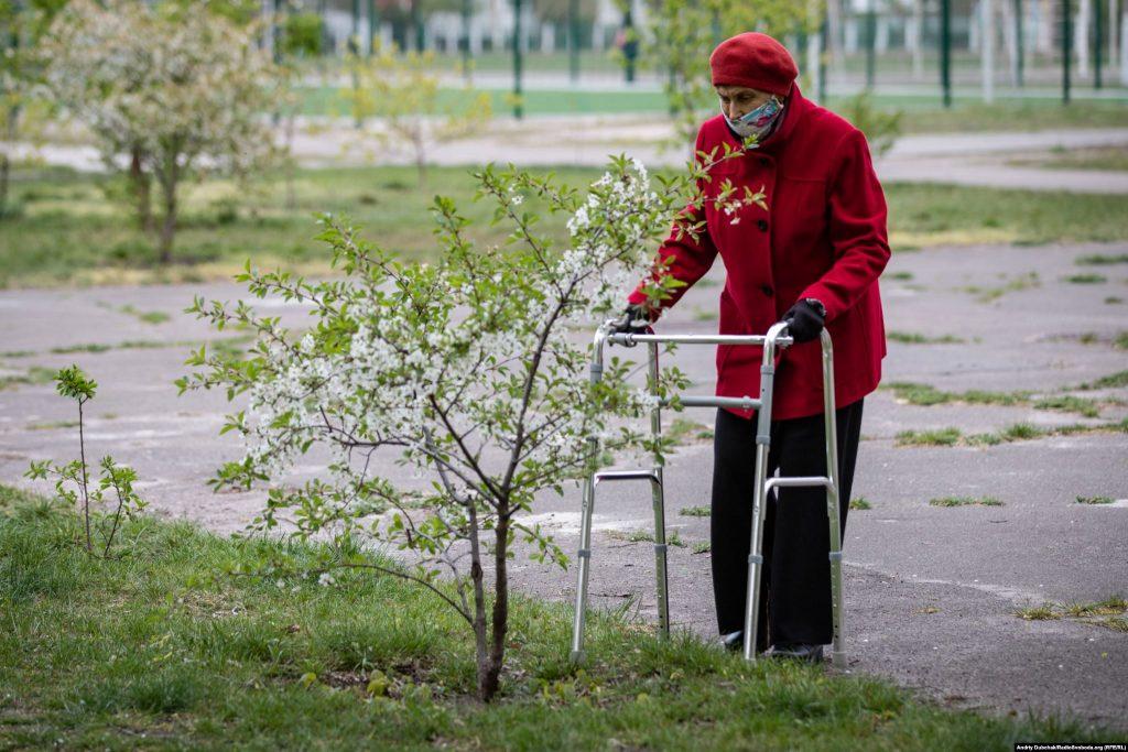 Літня жінка з ходунками біля вишні. Фото - Андрій Дубчак