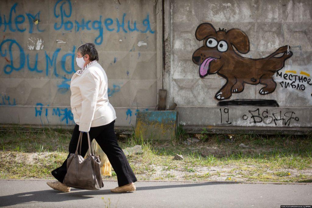 Жінка у медичній масці йде з торбами продуктів додому з магазину повз паркан зі смішним графіті. Фото - Андрій Дубчак